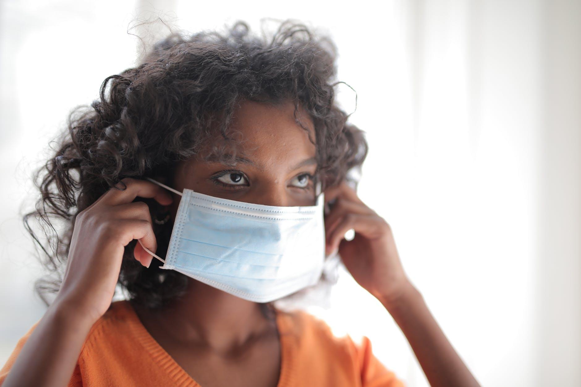 woman in orange crew neck shirt wearing white face mask